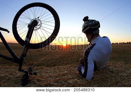 resting cyclist with a Bicycle looks at sunset