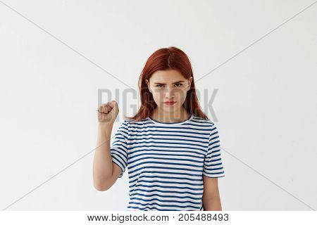 Aggressive young woman keeping her fist ready to fight and defend herself against injustice or violence. Strong woman showing pumped fist at camera as sign of girl power feminism and independence