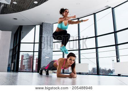 Two sporty Caucasian girls doing partner circuit workout, first woman holding plank position while the partner is squat side jumping over her in sports club.
