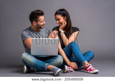 A beautiful young couple sitting on the ground and looking at a laptop and smiling