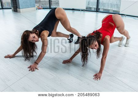 Two sexy brunette women wearing leotards doing downward dog calf stretch exercise on floor in gym during stretching class.