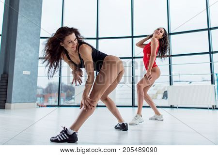 Two slim athletic female models wearing swimsuits and sneakers smiling standing in sexy playful pose or dancing indoors.