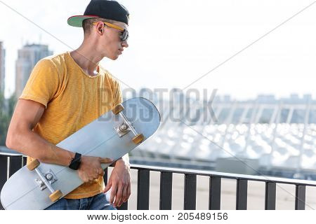 Side view serene boy looking away from bridge while holding board in arms outdoor. Copy space