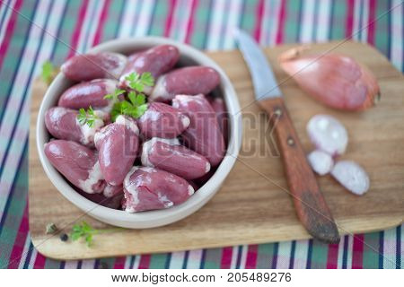 Raw chicken hearts in a bowl on wooden.