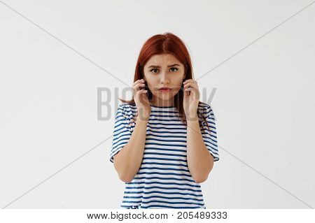 Body language. Picture of beautiful anxious worried young woman in striped t-shirt touching her face frowning and staring at camera. Anxiety worry stress frustration and negative feelings