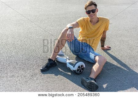 Full length portrait of cheerful teenager sitting on asphalt near gyroscope. Copy space