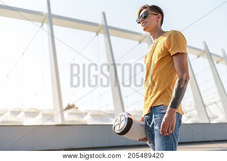 Low angle side view outgoing teenager holding digital device in hand. Copy space