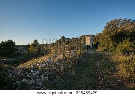 Small military pillbox in ruined base at sunset