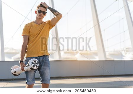 I am so cool. Serious teenager passing hand over head while keeping gyroboard in arm. Gadget concept. Copy space