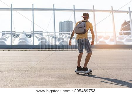 Full length teenager riding on gyroscope while flourishing arms at street. He turning back to camera. Copy space