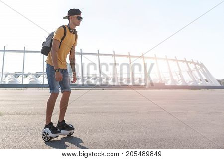 Full length side view cheerful teenager going on hoverboard at street in sunny day. Copy space