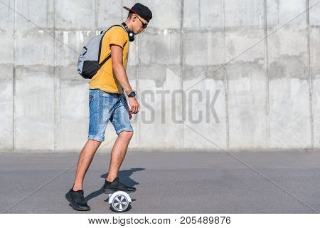 Full length side view serious boy riding on digital device outdoor. Copy space