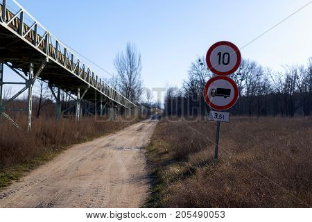 Long dirt road up ahead with danger sign