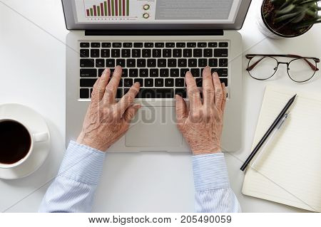 People age modern technologies and e-commerce concept. Cropped shot of retired woman typing on laptop earning money via internet sitting at home office drinking coffee and making notes