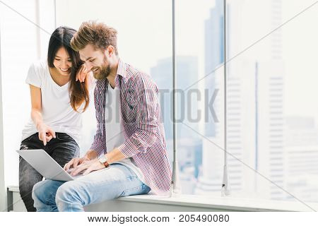 Multi-ethnic young couple or college student using notebook laptop together in campus or office. Information technology education startup business or modern lifestyle concept. With copy space