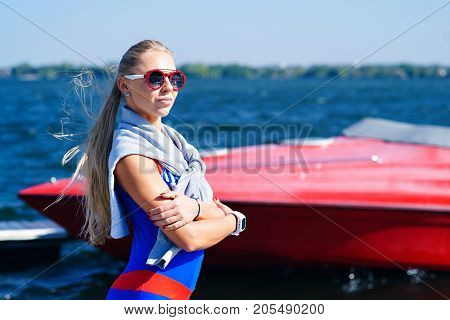 Portrait of a fitness girl on a red yacht background