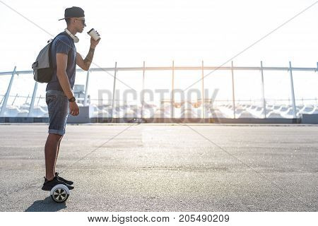 Side view serious young man tasting mug of hot beverage while riding on hoverboard. Copy space