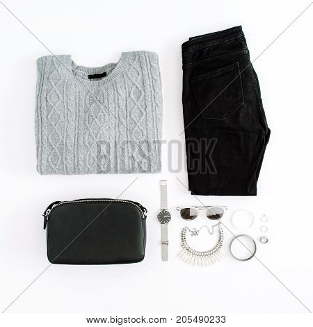 Women's fashion clothes and accessories on white background. Flat lay female styled look with warm sweater jeans purse watch sunglasses. Top view.