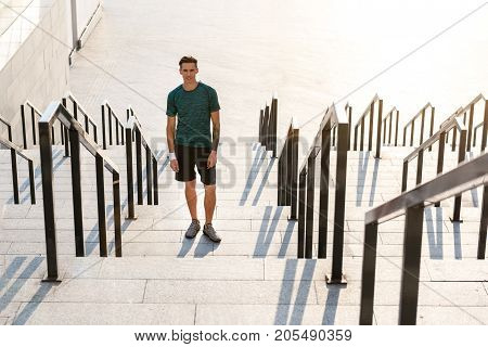 Full length portrait of cheerful young sportsman situating on stairs. Copy space