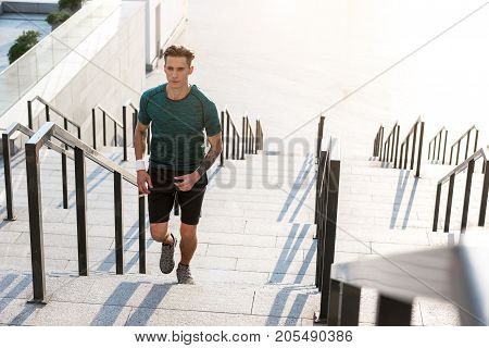 Full length portrait of serene male athlete running on footway. Sport concept. Copy space