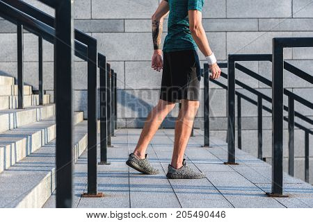 Close up male legs running on stairs at street. Sport concept