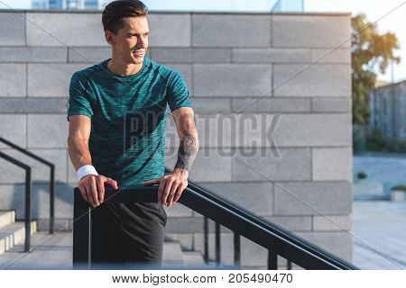 Portrait of smiling young athlete having rest after workouting outdoor. He leaning on handrail of footway