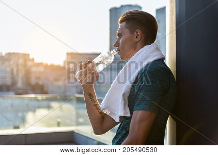 Side view serene male athlete drinking bottle of water after good training outdoor. Copy space