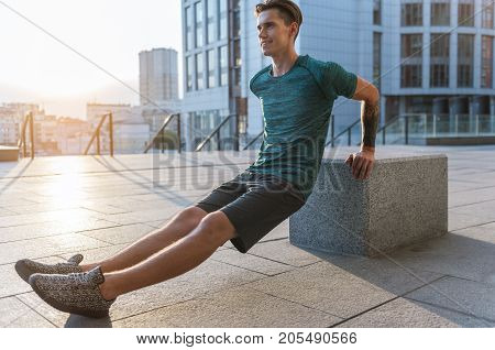 Full length side view outgoing male athlete making exercises at street. Copy space