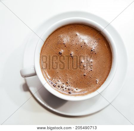 Cappuccino or hot chocolate with frothy foam white coffee cup top view closeup isolated on white background.
