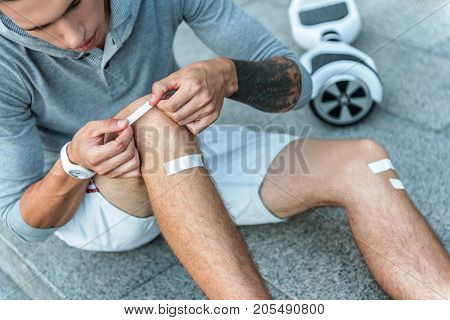 Close up male athlete applying adhesive bandage while sitting on floor outdoor near hoverboard. Injury concept