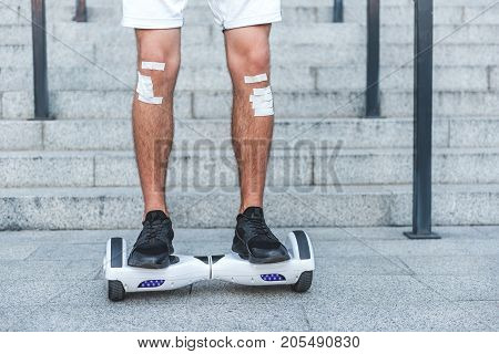 Close up male legs with adhesive bandage riding on giroscooter outdoor. Injury concept