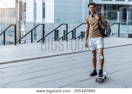 Full length portrait of cheerful young man riding on skate at street