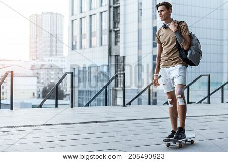 Full length portrait of outgoing male athlete going on board outdoor. Copy space