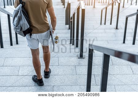 Male athlete going down descending on rungs while keeping board and bag in arm