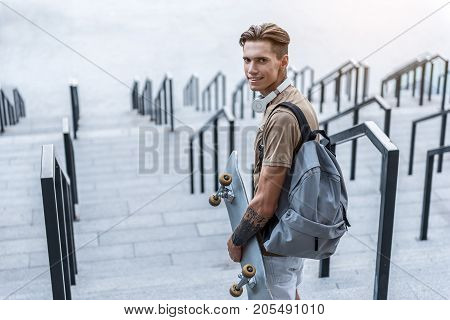 Portrait of cheerful man holding skate in hand at street. He looking at camera