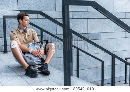 Full length side view cheerful student sitting at streetnear skateboard. Rest concept. Copy space