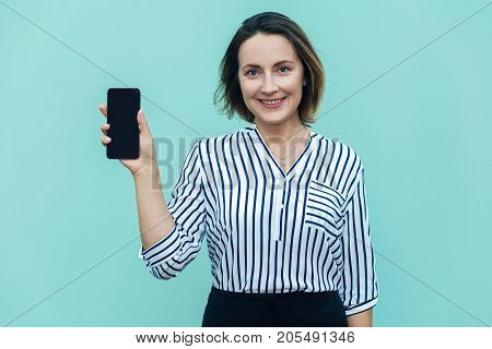 Success And Beautiful Business Woman Showing New Smart Phone And Looking At Camera With Toothy Smile