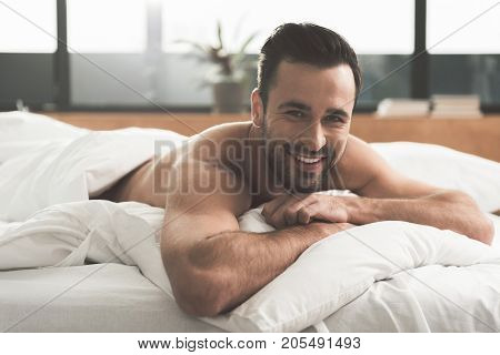 Portrait of excited young man awaking in his bed with happiness. He is looking at camera and laughing. Good morning concept