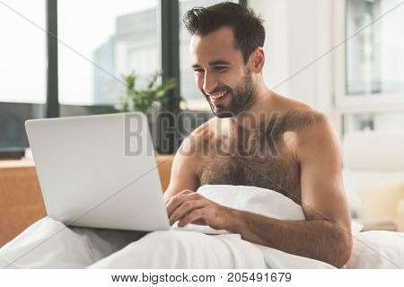 Portrait of joyful young guy typing on laptop in the morning. He is sitting covered by blanket in bedroom and laughing