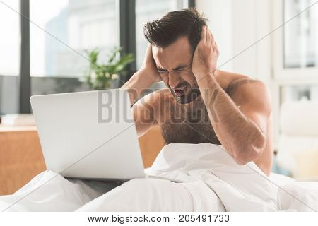 Overworked. Tired young man feels terrible headache while working on computer. He is sitting on bed half naked and touching his head with pain