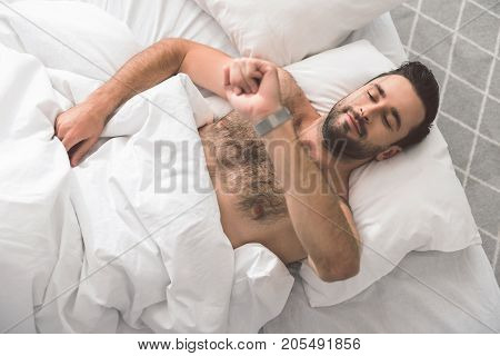 Having more time for sleep. Top view of cheerful young man looking at his watch and smiling. He is lying on comfortable bed at home