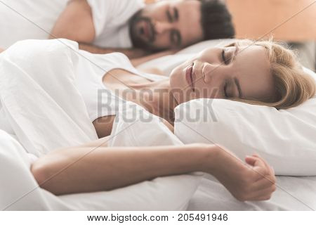 Portrait of happy young woman sleeping next to her husband on bed. She is smiling with enjoyment
