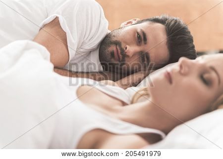 I am the happiest man ever. Portrait of cheerful young man enjoying dreams while lining near sleeping woman. He is looking at camera with joy