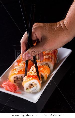 Japanese sushi rolls dish with hand holding one pice in chopsticks on black