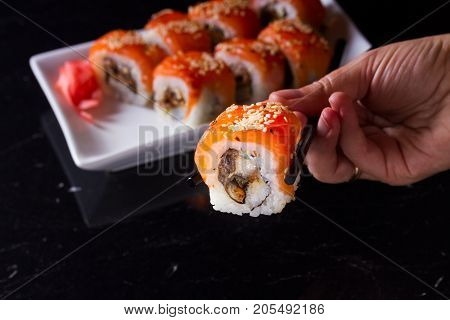 Japanese sushi rolls dish with hand holding one pice in chopsticks, low key