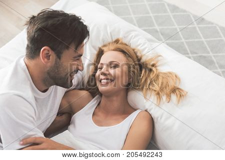 Top view of excited young man and woman are laughing while luxuriating in bed. They are hugging with love