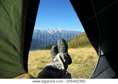 leg tourist in boots out of the tent with mountains in the background