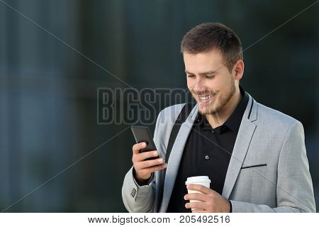 One happy executive reading a mobile phone message and holding a take away drink walking on the street