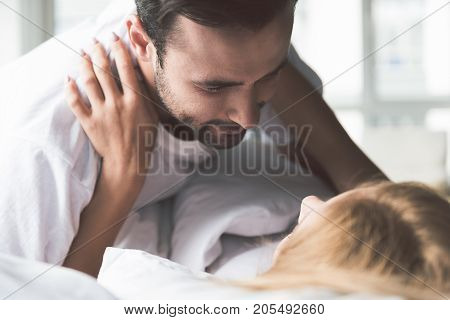 You are love of my life. Portrait of affection young man looking at woman with admiration. They are lying on bed and hugging