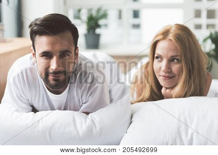 Portrait of happy loving couple lying on bed with relaxation and smiling. Lady is looking at her husband with love